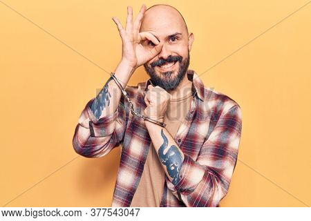 Young handsome man wearing prisoner handcuffs smiling happy doing ok sign with hand on eye looking through fingers