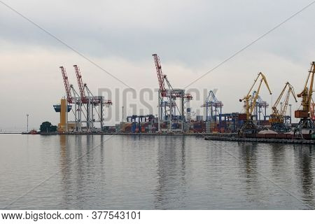 Containers In The Port. Harbor Cranes In Cloudy Weather.