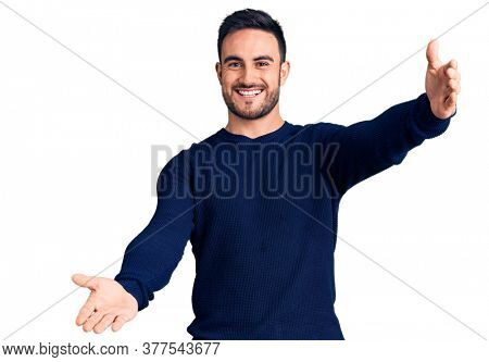 Young handsome man wearing casual clothes looking at the camera smiling with open arms for hug. cheerful expression embracing happiness.