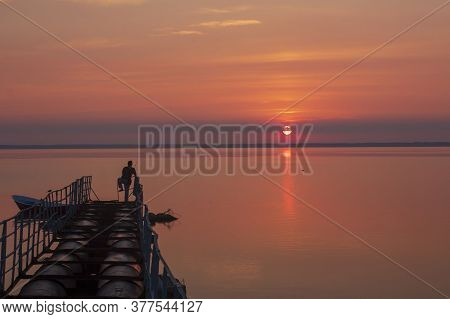 Sunny Dawn Over The Lake. Morning Fishing. Fisherman With A Fishing Rod. Fisherman's Boat.