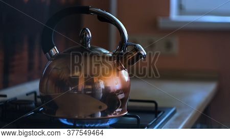 Close Up Of A Stainless Steel Tea Kettle On A Flaming Gas Stove. Concept. Heating Kettle With The Re