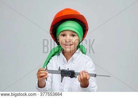 Little Boy In A Construction Helmet. Shows The Caliper. Advertising Concept For The Construction