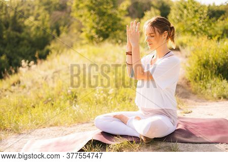 Happy Young Woman Is Meditating In Lotus Position With Closed Eyes Sitting On Yoga Mat On Grass. Fem