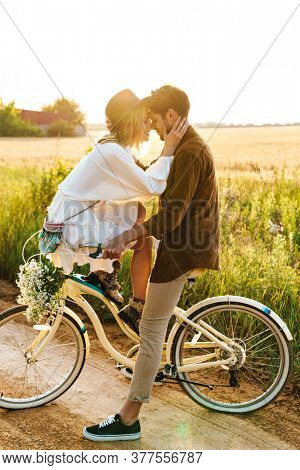 Image of young caucasian couple kissing while riding bicycle together in countryside