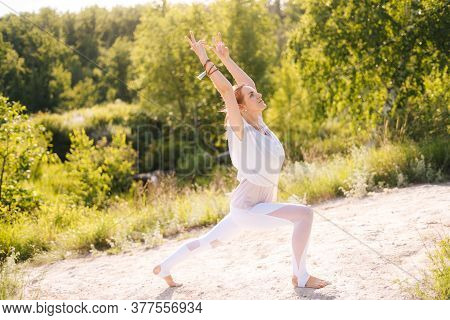 Relaxed Young Woman Doing Yoga Warrior Pose On Clear Sunny Day At Nature. Girl Yoga Instructor Is Pe