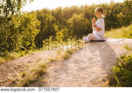Side View Of Young Woman Meditating In Lotus Position With Closed Eyes Sitting On Yoga Mat. Female Y