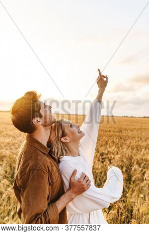 Image of young caucasian couple hugging and gesturing finger upward at sky in golden field