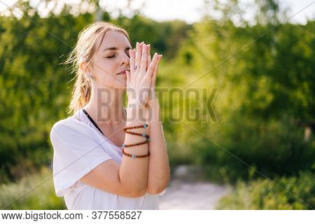 Close-up Of Face And Hands Of Young Relaxed Woman With Emotion Of Serenity And Tranquility Performin