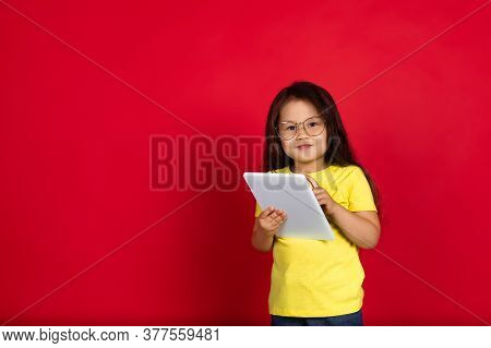 Using Tablet. Beautiful Little Girl Isolated On Red Background. Half-lenght Portrait Of Happy Child