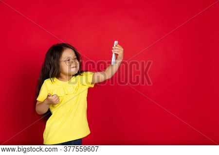 Taking Selfie. Beautiful Little Girl Isolated On Red Background. Half-lenght Portrait Of Happy Child