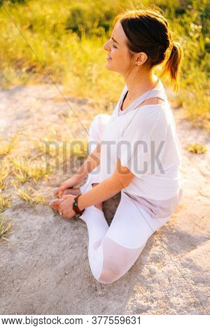 Portrait Of Meditative Young Woman Meditating Sitting In Lotus Position With Closed Eyes, Outside In