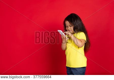 Scrolling Phone. Beautiful Little Girl Isolated On Red Background. Half-lenght Portrait Of Happy Chi