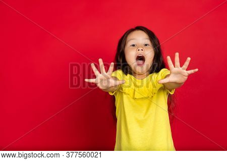 Palms Open. Beautiful Little Girl Isolated On Red Background. Half-lenght Portrait Of Happy Child Ge
