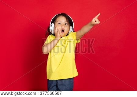 Pointing Shocked, Wearing Headphones. Beautiful Little Girl On Red Background. Half-lenght Portrait
