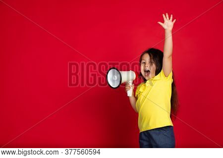 Shouting With Megaphone. Beautiful Little Girl On Red Background. Half-lenght Portrait Of Happy Chil