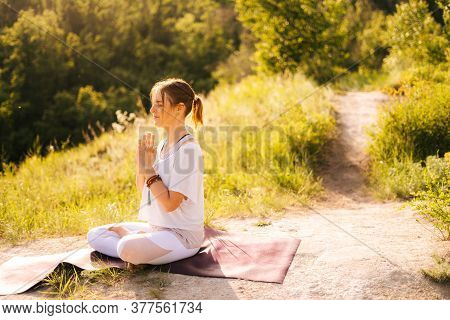 Relaxed Young Woman Is Meditating In Lotus Position With Closed Eyes Sitting On Yoga Mat. Female Yog