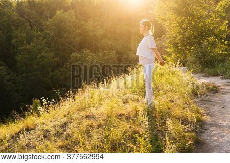 Young Woman Practicing Yoga Outdoor In Nature Outdoors In Evening At Sunset. Girl Warms Up Before Th