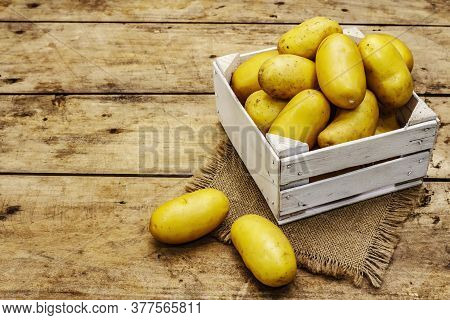 Whole Unpeeled Raw Potatoes In A Wooden Crate