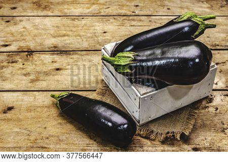 Whole Unpeeled Raw Eggplants In A Wooden Crate