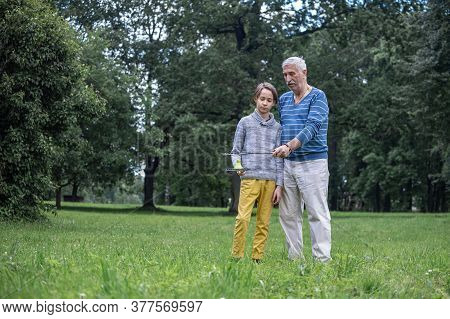 Boy And Grandfather In The Park In Summer, Badminton Rackets And Shuttlecock In Hands, Active Lifest