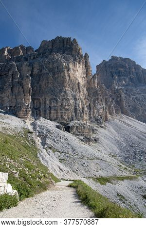 Scenery Of The Italian Dolomites, Massifs Of Mountains And Green Meadows On A Background Of Blue Sky