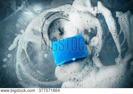 In The Kitchen Sink Is A Blue Sponge For Washing Dishes, Which Was Used With Soap To Wash The Sink T
