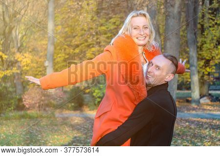Middle-aged Couple In Autumn Park. Smiling Man Holding Woman In Hands On Colorful Fall Background. H