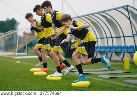 Youths On Stability Soccer Training On Balance Cushions. Sports Balance Training. Young Soccer Playe