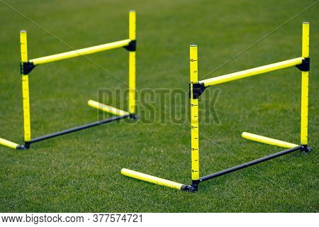 Yellow Training Hurdles On Sports Training Field. Two Hurdles In Line For Jumping Practice. Physical