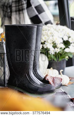 Black Rubber Rain Boots, Or Wellies, Sitting On Front Porch Decorated For Autumn.