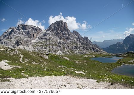 View Of A Mountain Massif With Clouds In The Blue Sky, Rock Lake Lined  Green Meadow With Flowers, S