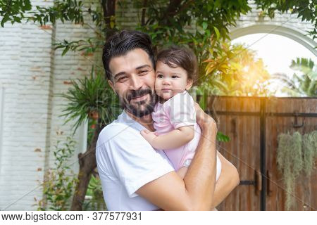 Happy Handsome Father Holding Adorable Little Baby Daughter At House With Happiness And Smile Face.