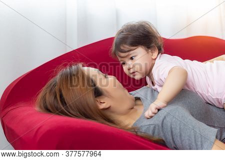 Infant Baby Or Adorable Little Mix Race Baby Look At Her Asian Mother And Lying Down On Her Mother C