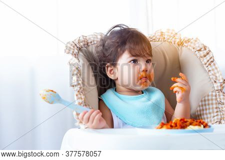 Adorable Hungry Toddler Girl Or Infant Baby Eating Delicious Spaghetti Food With Tomato Sauce On Bab