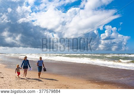 Pape / Latvia - July 6 2020: Family Walking Together On A Beautiful Sandy Beach With Baltic Sea And