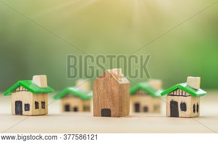 Wooden House In Among Green House For Real Estate. Planning Savings Money Of Coins To Buy A Home Con