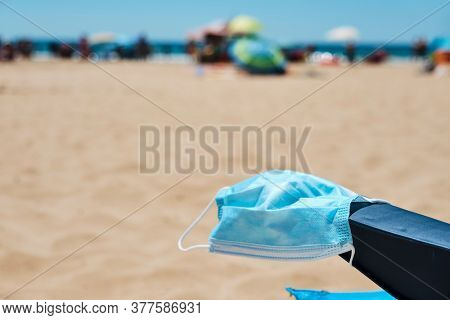 closeup of a surgical mask on the armrest of a blue deck chair on the beach, with the ocean in the background