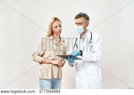 Professional Male Doctor In Medical Uniform And Protective Mask Using Digital Tablet And Explaining