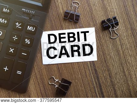 White Paper With Text Debit Card On A Wooden Surface With Stationery