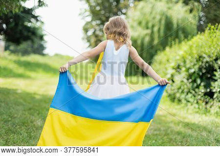 Child Carries Fluttering Blue And Yellow Flag Of Ukraine In Field. Ukraine's Independence Day. Flag