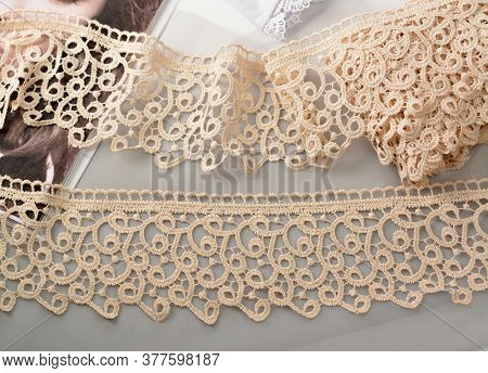Tapes Of Beige Gentle Guipure, Beauty Lace Fabric On Light Background. Elastic Material. Using For A