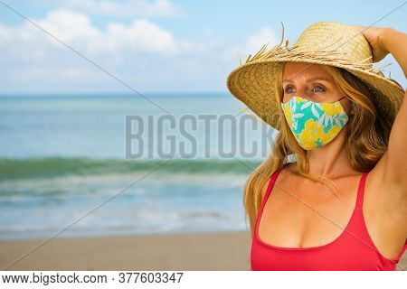 Funny Portrait Of Young Woman In Straw Hat On Tropical Sea Beach. New Rules To Wear Cloth Face Cover