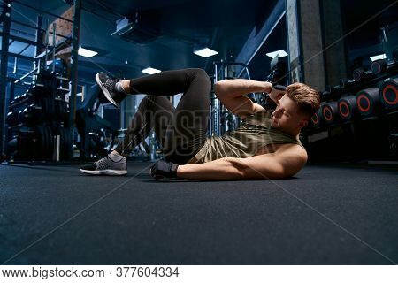 Muscular Caucasian Man Training Abs On Floor In Sports Club. Side View Of Handsome Young Sportsman B
