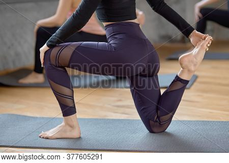 Crop Of Young Fit Women Doing Horse Rider Exercise, Anjaneyasana Pose In Spacy Gym, Loft Interior. S