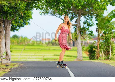 Young Woman Riding On Skateboard. Happy Woman Have A Fun On Empty Road. Active Family Lifestyle, Out