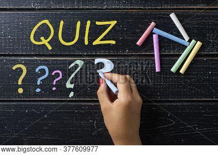 A Female Hand Writes The Word Quiz On The Blackboard.