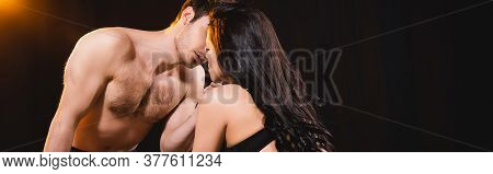 Panoramic Concept Of Shirtless Man Kissing Woman In Bra On Black