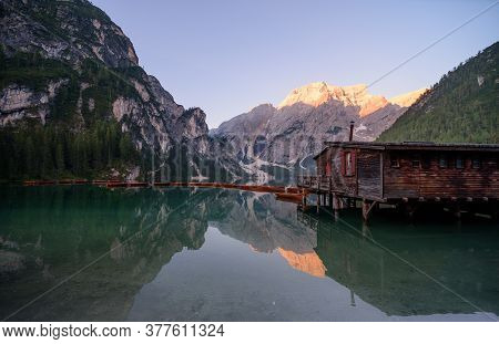 The Seekofel Mountains And Wooden Boats Reflected In The Waters Of Lake Braies At First Light In The