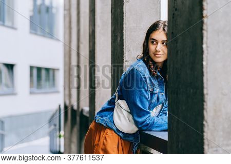 Brown Haired Girl In Casual Clothes Posing On Parapet In City Outdoor With Urban Background. Portrai
