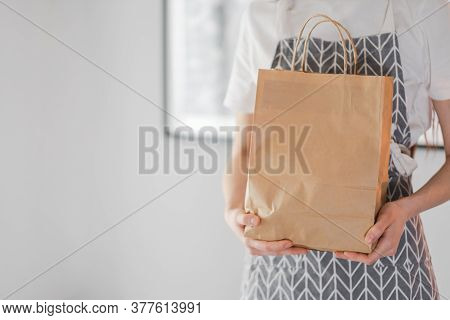 Woman Holds Craft Eco Shopping Bag In Hands, Take Away. Delivery Food, Mock Up. High Quality Photo